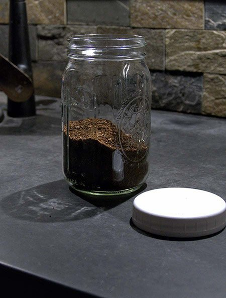 Coffee grounds sit in a mason jar before cold water is added to them to make cold brew coffee.