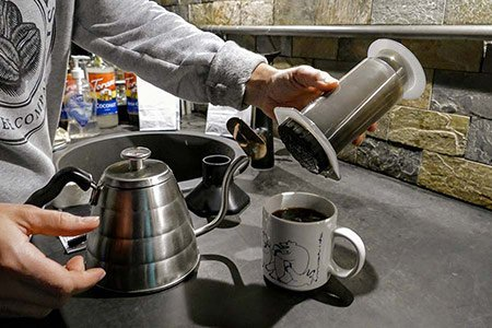 A coffee roaster lifts the brew chamber from the top of a coffee mug and adds more water to the cup.
