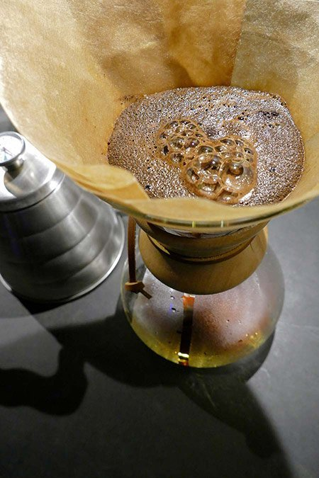 Coffee grounds bloom in the filter of a Chemex coffee maker.