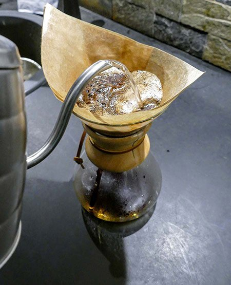 A coffee roaster demonstrates how to pour a second batch of water into a Chemex coffee maker.