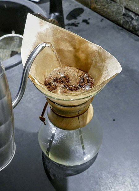 A coffee roaster demonstrates how to pour water into a Chemex coffee maker.