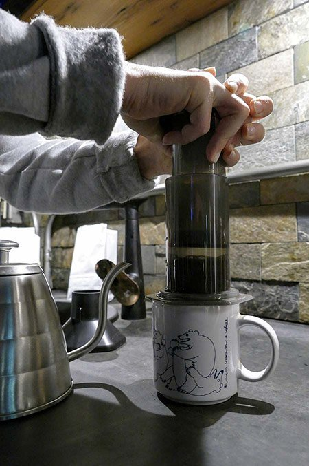 A coffee roaster demonstrates how to slowly plunge coffee in Aeropress chamber.