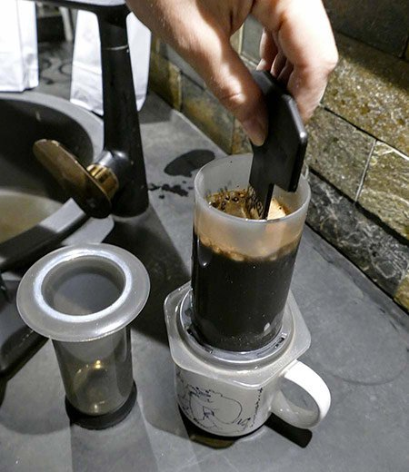 A coffee roaster demonstrates how to stir coffee in an Aeropress brew chamber.