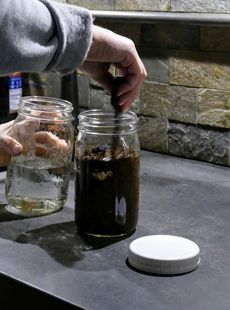 A coffee roaster stirs coffee grounds and cold water into a mason jar to make cold brew.