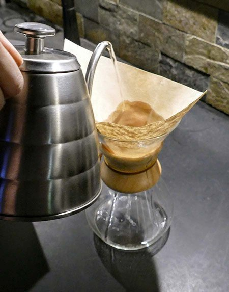A coffee roaster demonstrates how to rinse a Chemex coffee filter.
