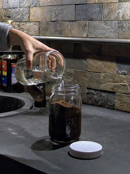 A coffee roaster pours cold water over coffee grounds in a mason jar to make cold brew.